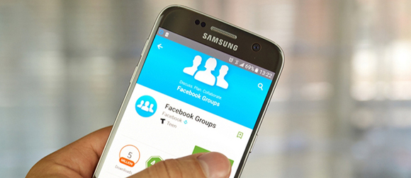 Hand holding phone showing Facebook Groups App