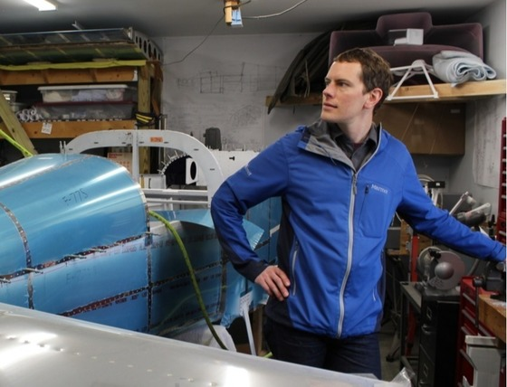 Jeff Toaddy, wearing a blue windbreaker, stands in his shop next to the plane he's building