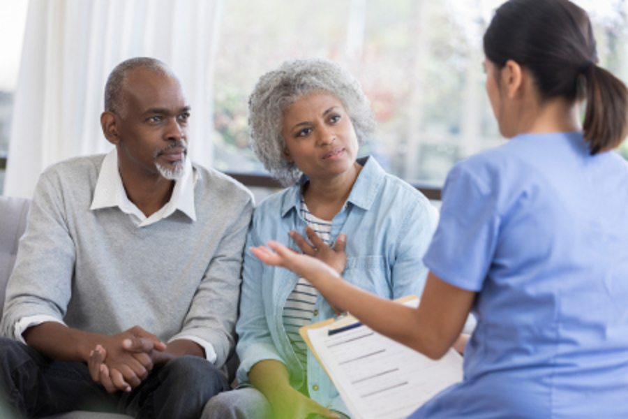 Couple talks to doctor about medical costs.