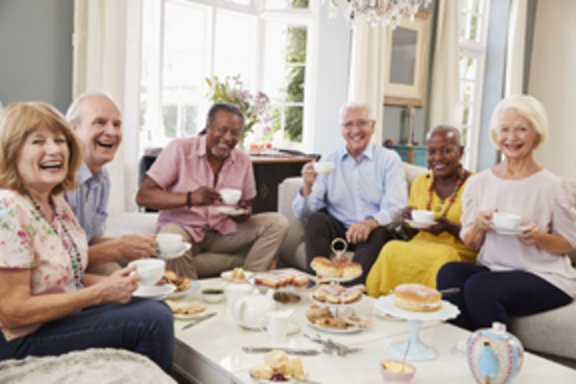 A group of older adults having brunch and smiling.