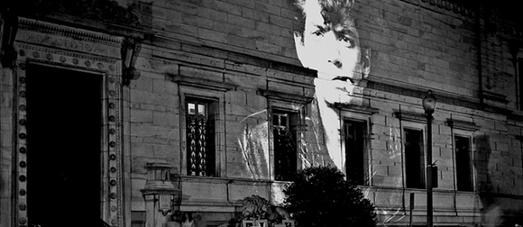 An image of Robert Mapplethorpe being projected on the Corcoran building