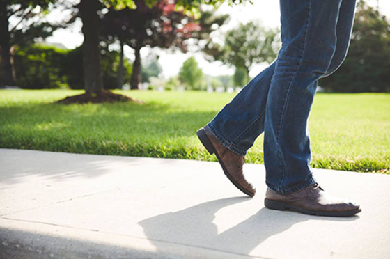 Persons legs and feet walk on a sidewalk with grass and a tree beside them