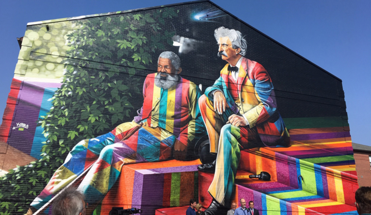 The mural depicts Mark Twain and his friend, John T. Lewis. Located at 1188 Hertel Avenue in Buffalo, NY, next to Ristorante Lombardo.