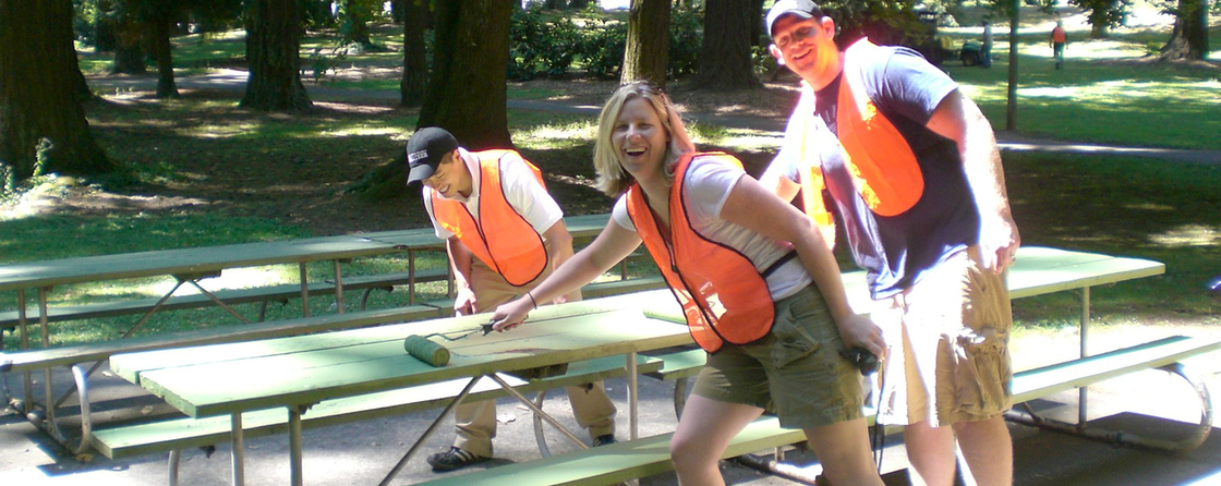 Volunteers painitng picnic tables