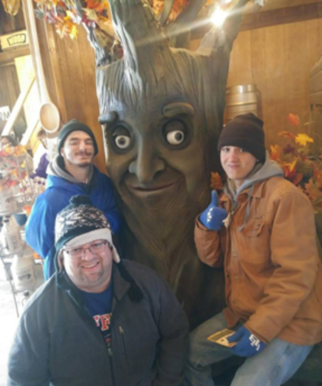 Lockport Recreational Respite participants pictured with a faux tree that has a kindly face at Wolf Maple Products in Middleport