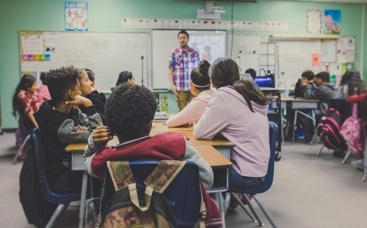 Kids in a classroom listening to a teacher