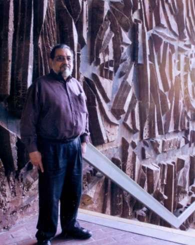J Sergio O Cadiz in front of the Cypress College Complex mural he created