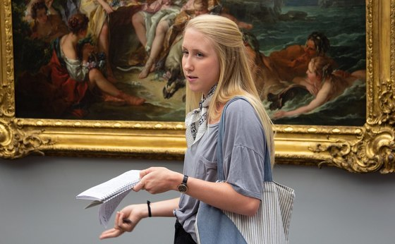 Student standing in front of a painting in the Louvre in Paris, France.