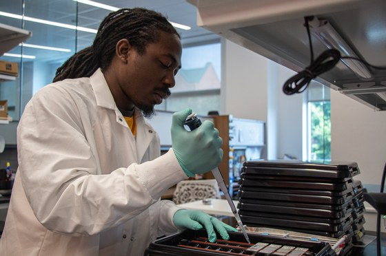 John Lawrence III uses a pipette to conduct research in The Schulz Lab in Summer 2019