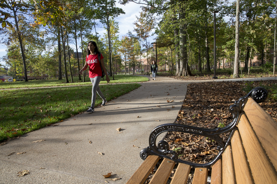 Female-presenting student walking past a bench outside. She is wearing a red Miami shirt.
