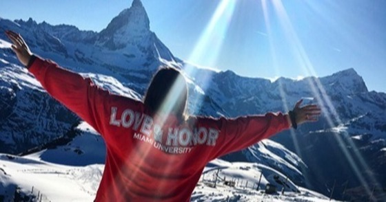 """student stands in front of snowy mountains, arms outstretched, wearing a red """"love and honor"""" sweatshirt"""