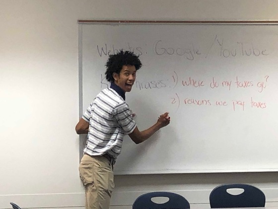 """Man stands at whiteboard that says """"Where do my taxes go?"""""""