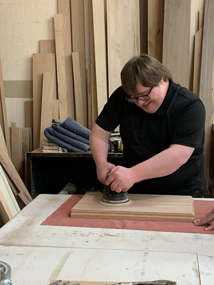 Young man at his internship cutting wood in a woodshop