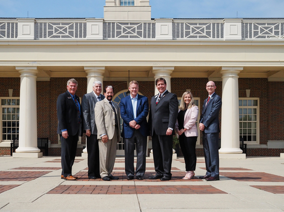 Photo standing in front of VOA Learning Center of Chamber and State leaders