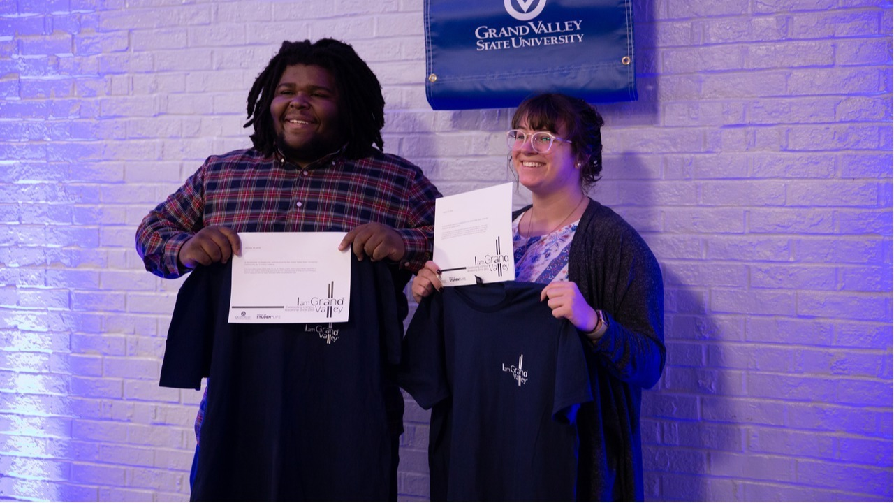 Two students presenting their I am GV awards and shirts.