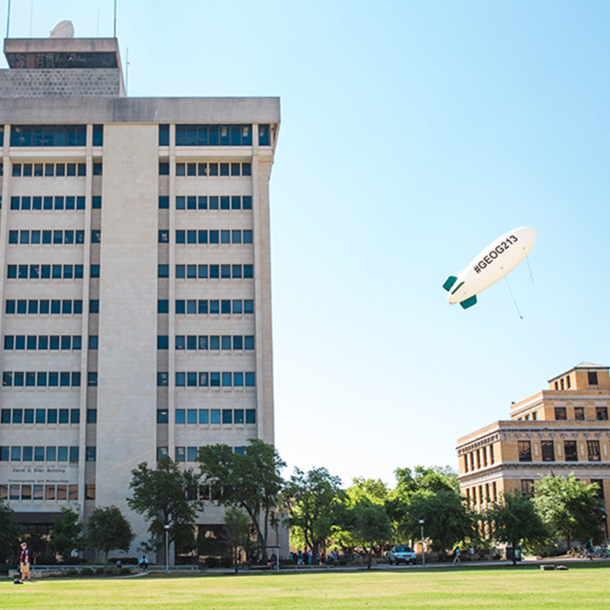 The Geography 213 blimp in front of the O&M Building. (Photo by the Texas A&M Foundation.)
