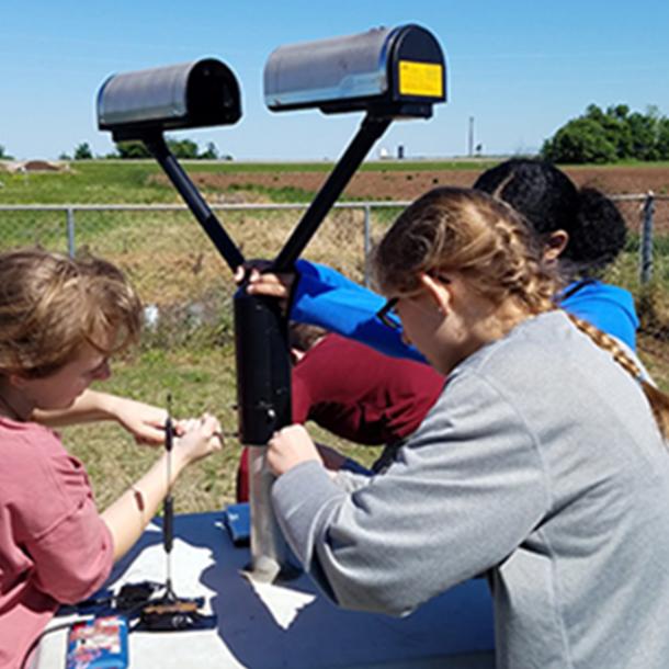 Undergraduate students Rachel Eldridge, Leanne Blind-Doskocil, and Erin Sherman (L to R) assembling the disdrometer. (Photo courtesy of Dr. Don Conlee.)