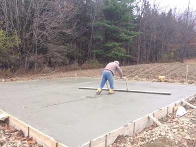 Mason levels the concrete for garage foundation
