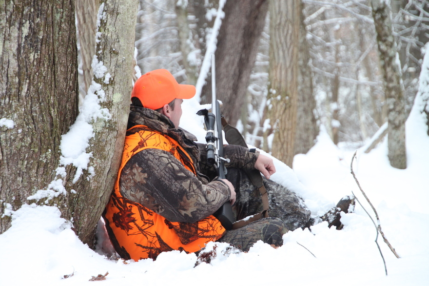 A hunter in camo and orange clothes sits next to a tree in the snow with a gun.