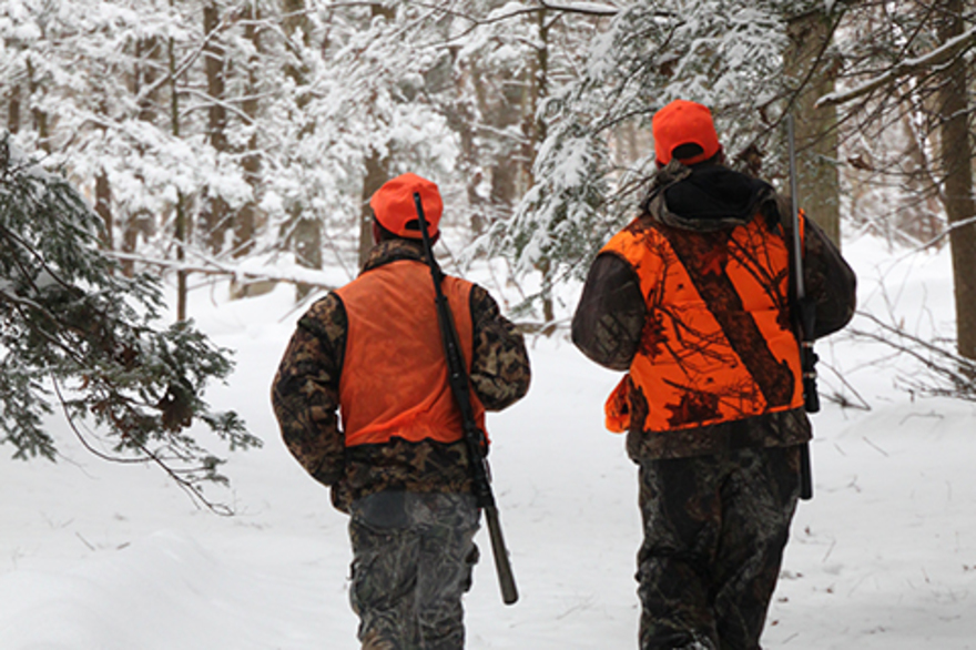 Two hunters wearing camo and orange clothes walk through a snowy forest with rifles on their shoulders.