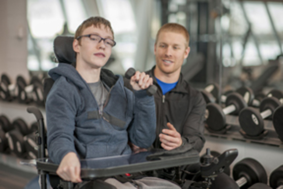 Young male direct support professional helping a young man who is living with a disabilty.