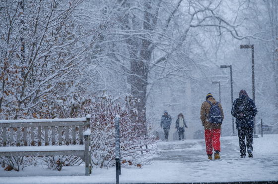 students walk outside past a bench in a snowstorm