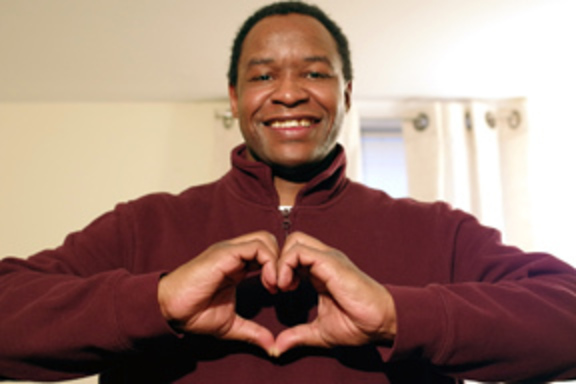 Program particiant Bernard making a heart gesture shape with his hands.