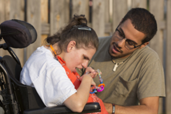 Direct care support professional pictured with a young woman living with a disability.