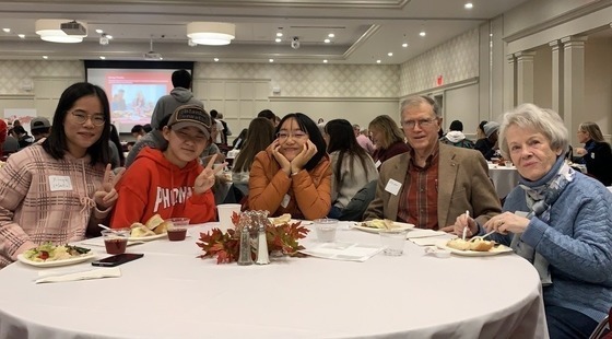 Three international students sit next to an older couple at a dinner