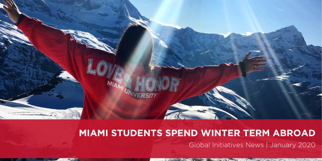 Miami students spend winter term abroad. Global Initiatives News January 2020. A photo shows a girl wearing a love and honor shirt stands with her arms spread out in front of snowy mountains