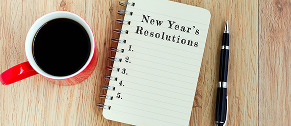 """Cup of coffee, pen and notebook with words reading """"New Year's Resolutions"""" and blank list on table"""