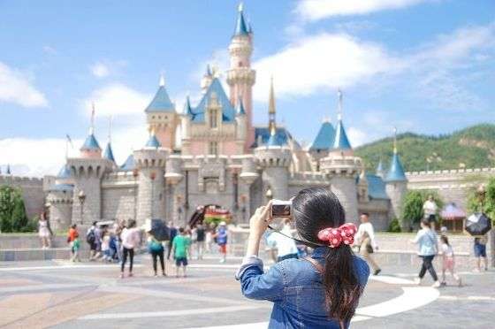 a girl takes a picture of the disney castle