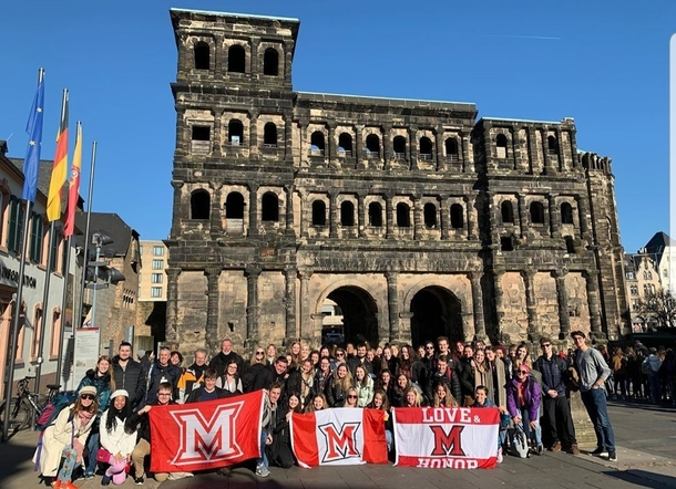 MUDEC students in front of Porta Nigra with three Miami flags