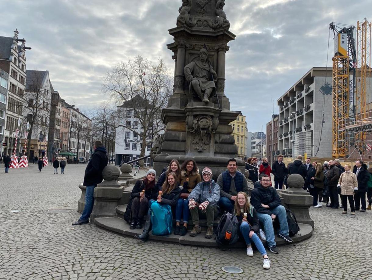Students on the steps of a statue on Cologne, Germany