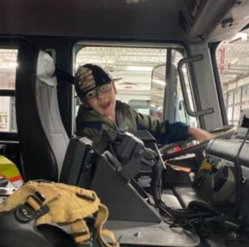 A child from Northtowns Afternoon Respite sitting in the drvers' seat of a firetruck.