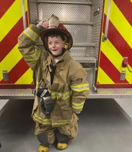 a child from Northtowns Afternoon Respite in real firemen firefighting clothes.