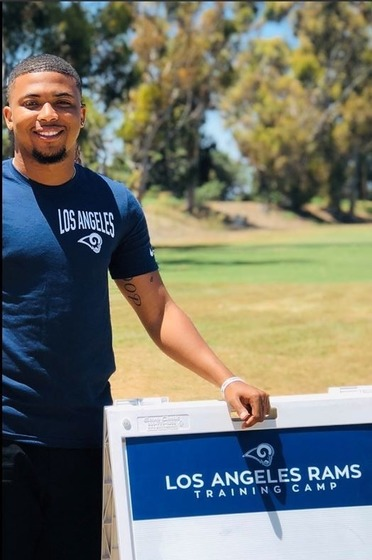 A'mon Yisrael next to Los Angeles Rams Training Camp sign