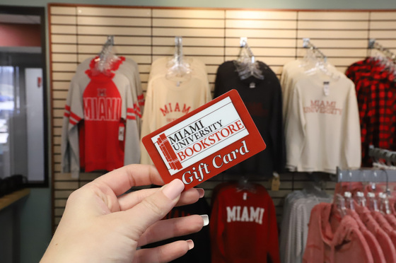 Miami University Bookstore gift card held up in front of Miami shirts