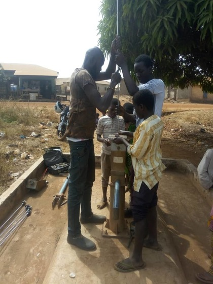 Group of males working on water pump