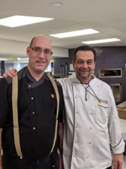 A photo of a supported employment professional posing with a colleague both are wearing restaurant uniforms.