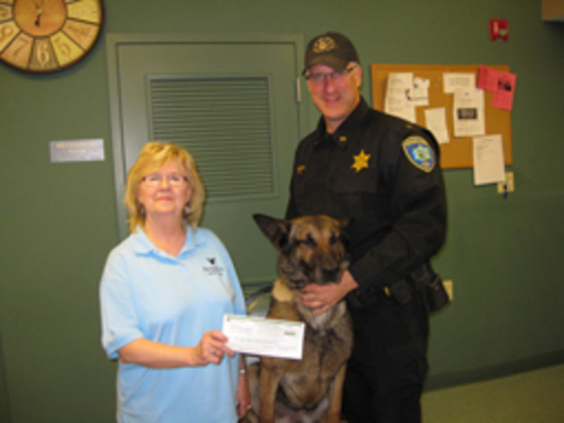 A photo of a canine officer and his handler being presented a check by a People Inc. staff member.