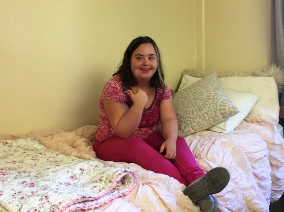 Young woman sits on bed in college dorm room