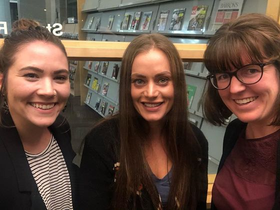 Three woman in library smile at camera