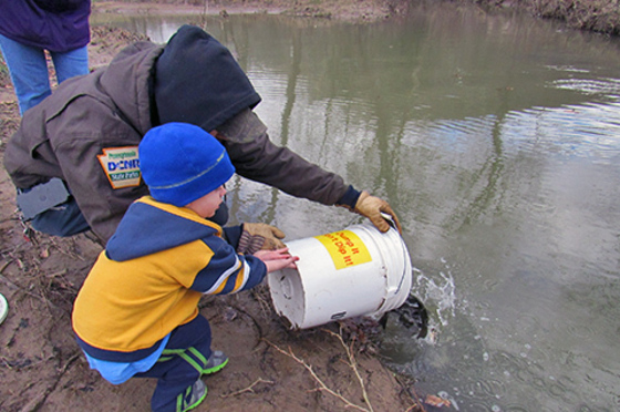 A person helps a child dump a bucket of water and fish int oa creek on a muddy bank.