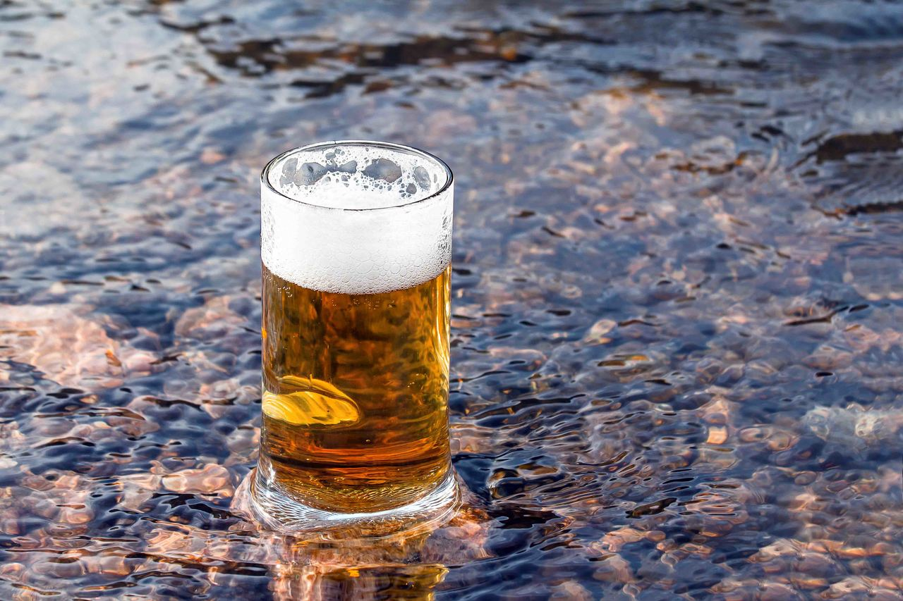 A mug of beer sits in shallow water of a creek