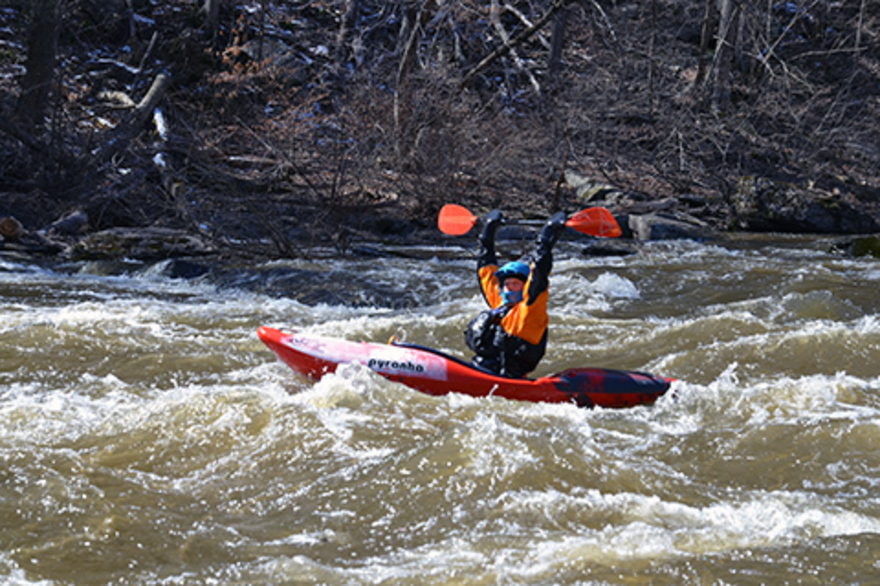 A person rides a kayak in a turbulant water while holding a paddle over their head