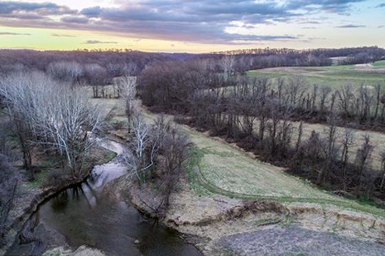 A creek flows past green fields