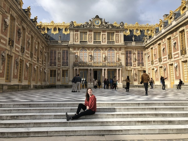 MUDEC student on steps at Palace of Versailles
