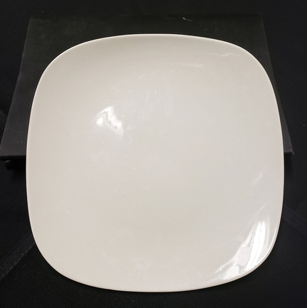 Photo of a cream colored square plate with soft edges (almost circular) formerly used in Rohr's. The rectangular piece is divided into three squares to serve three different items. It will be sold at the dinnerware sale on Saturday, March 14 from noon to 4 p.m. at the Morris Inn.