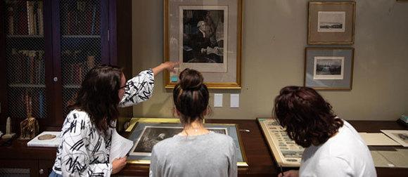 Three women examine a display about George Washington